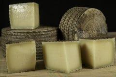 Los quesos de Manchego Curado, uno de ellos cutted en pedazos Fotos de archivo