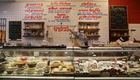 Los quesos, los cortes fríos y las salmueras en la exhibición en Gramercy parquean tienda de delicatessen Imagen de archivo libre de regalías