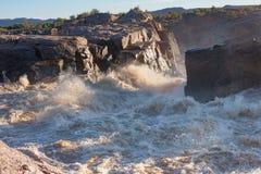 Los rápidos turbulentos como el río anaranjado, en la inundación llena, las razas hacia el Augrabies espectacular caen Fotos de archivo