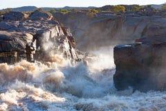Los rápidos turbulentos como el río anaranjado, en la inundación llena, las razas hacia el Augrabies espectacular caen Imagen de archivo libre de regalías