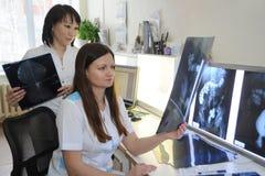 Los radiólogos de los doctores trabajan en el laboratorio con las fotografías de la radiografía imagen de archivo