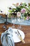 Los ramos de flores rosadas en una tabla fijaron para la cena con las velas Imagen de archivo libre de regalías