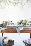 Los ramos de flores rosadas en una tabla fijaron para la cena con las velas Fotos de archivo libres de regalías