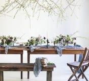 Los ramos de flores rosadas en una tabla fijaron para la cena con las velas Imagenes de archivo
