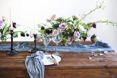 Los ramos de flores rosadas en una tabla fijaron para la cena con las velas Imágenes de archivo libres de regalías