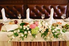 Los ramos de rosas mienten en la mesa de comedor servida Fotografía de archivo libre de regalías