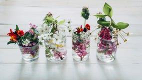 Los ramos pintorescos de primavera colorida florecen en las botellas de cristal de los floreros, colocándose en fila en una tabla Imagen de archivo libre de regalías