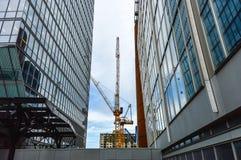 Los rascacielos altos y la grúa de construcción i del negocio Imagen de archivo libre de regalías