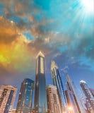 Los rascacielos céntricos de Dubai en la noche, hacia el cielo ven Imagen de archivo libre de regalías