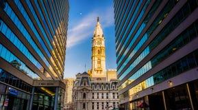 Los rascacielos y la tarde se encienden en ayuntamiento en Philadelp céntrico Imagen de archivo libre de regalías