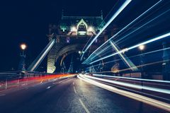 Los rastros de la luz de la ciudad del tráfico en torre tienden un puente sobre Londres en la noche imagen de archivo