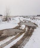 Los rastros de la pisada del ` s del coche ruedan en el camino nevado del campo Imágenes de archivo libres de regalías