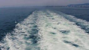 Los rastros del transbordador en el mar con blanco hacen espuma, lado trasero