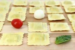 Los raviolis arreglaron en fila con el tomate, el bocconcini y la albahaca Fotos de archivo