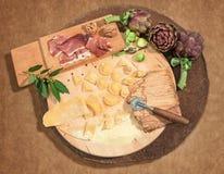 Los raviolis frescos hechos en casa con el prosciutto, nueces y alcachofa, establecieron el paso en una pieza central redonda rús Foto de archivo