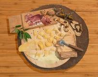 Los raviolis frescos hechos en casa con el prosciutto, nueces y setas, establecieron el paso en una pieza central redonda rústica Fotografía de archivo libre de regalías