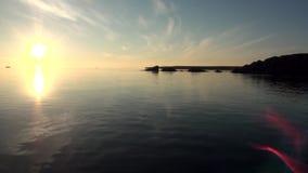 Los rayos brillantes de la puesta del sol en cielo reflejaron en superficie del agua del Océano ártico metrajes
