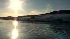 Los rayos brillantes del sol en cielo reflejaron en agua del Océano ártico en la nueva tierra almacen de metraje de vídeo