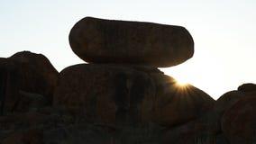 Los rayos de los soles aparecen sobre una roca inusual en los mármoles del diablo en el Territorio del Norte de Australia metrajes