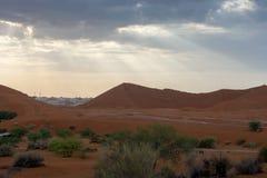 Los rayos de Sun perforan las nubes tempestuosas sobre las dunas de arena en los UAE fotografía de archivo