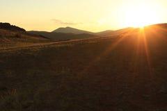 Los rayos pasados del sol poniente en las montañas Fotografía de archivo libre de regalías