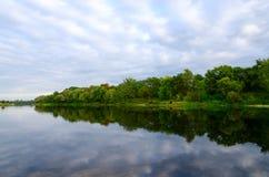 Los árboles en el banco de la charca y las nubes están reflejando en agua Fotos de archivo libres de regalías
