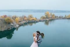 Los recienes casados elegantes de los pares están presentando antes de un lago en la colina Ceremonia de boda del otoño al aire l Fotos de archivo libres de regalías