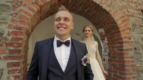 Los recienes casados están caminando en el castillo en su día que se casa La novia y el novio Enjoying en el día de boda almacen de video
