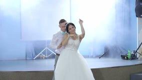 Los recienes casados felices bailan la primera danza en el restaurante metrajes