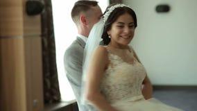 Los recienes casados felices bailan un vals en un cuarto con un interior hermoso en un hotel almacen de video