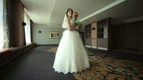 Los recienes casados felices bailan un vals en un cuarto con un interior moderno hermoso almacen de video