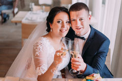 Los recienes casados felices beben el champán y el abarcamiento celebrando su nueva vida casada Foto de archivo libre de regalías