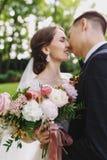 Los recienes casados felices novia y novio de los pares en una boda en parque del verde de la naturaleza se están besando Novia c foto de archivo
