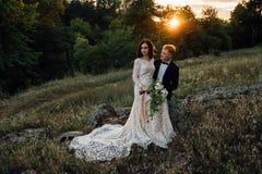 Los recienes casados felices se están sentando en una roca en la naturaleza Fotografía de archivo