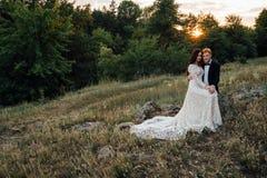 Los recienes casados felices se están sentando en una roca en la naturaleza Fotografía de archivo libre de regalías