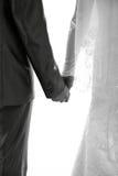 Los recienes casados llevan a cabo las manos de cada uno Foto de archivo