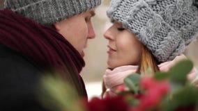 Los recienes casados preparan y el beso del abrazo de la novia y se calientan en bosque nevoso del pino durante las nevadas en la