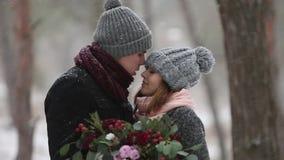 Los recienes casados preparan y el beso del abrazo de la novia y se calientan en bosque nevoso del pino durante las nevadas en la metrajes