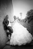 Los recienes casados que presentan en piedra caminan bw Fotografía de archivo