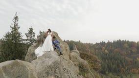 Los recienes casados se colocan en una alta cuesta de la montaña Novio y novia metrajes