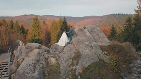 Los recienes casados se colocan en una alta cuesta de la montaña Novio y novia Opinión de Arial almacen de video