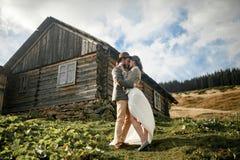 Los recienes casados se colocan y abrazan en fondo de la choza de madera vieja en soporte Imagenes de archivo