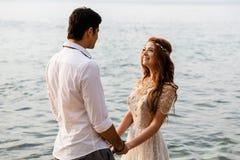 Los recienes casados se divierten en el agua en la playa foto de archivo