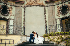 Los recienes casados sensibles son de abrazo y que se sientan en las escaleras del edificio viejo de Praga Fotografía de archivo