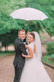 Los recienes casados sonrientes debajo del paraguas blanco que pasan su tiempo en el parque Fotografía de archivo libre de regalías