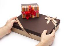 Los rectángulos de regalo son envueltos para arriba por las cintas en manos en un fondo blanco. Imagen de archivo libre de regalías