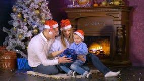 Los regalos abiertos de la Navidad de la familia feliz acercan a la chimenea del Año Nuevo de la Navidad metrajes