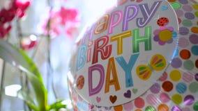 Los regalos de la celebración del cumpleaños presentan flores y un baloon que refleja la luz del sol almacen de video