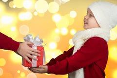 Los regalos de la Navidad del intercambio de los hermanos Las manos de niños con un regalo ¡Feliz Navidad y buenas fiestas! foto de archivo
