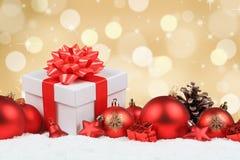 Los regalos de la Navidad presentan a bolas el copyspace de oro de la nieve de la decoración imagen de archivo